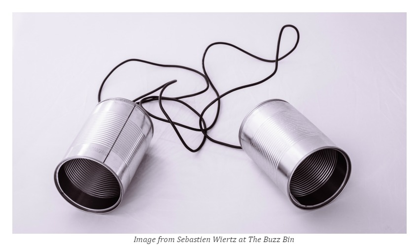 two telephone cans with long strings connected to each other