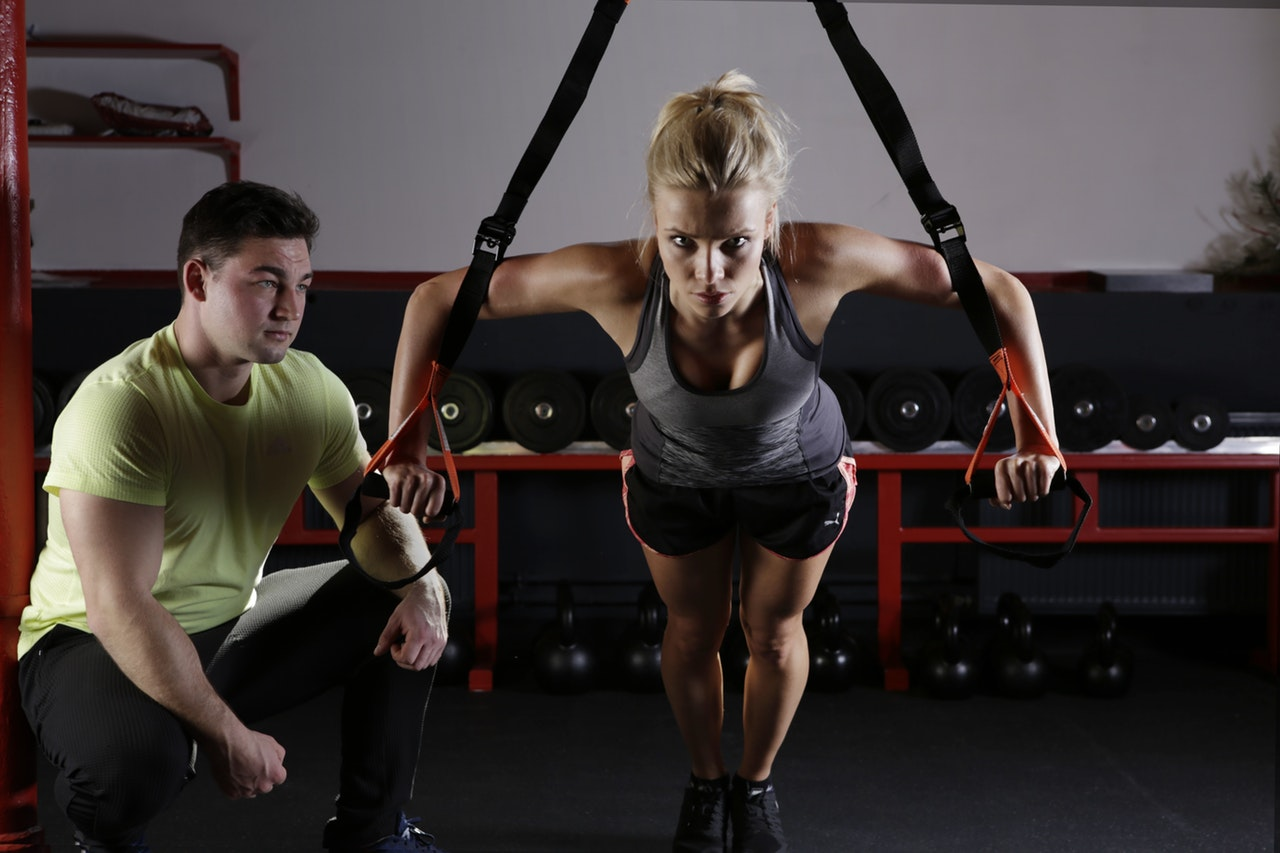 woman working out with a gym trainer
