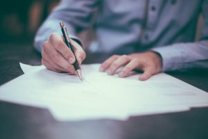 A professional signing his resume cover letter for a successful job search