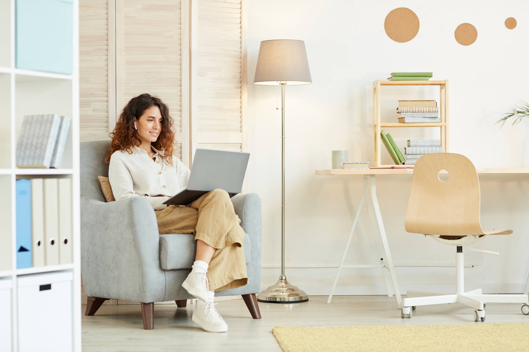 Woman sitting on a couch while using her laptop in her working space