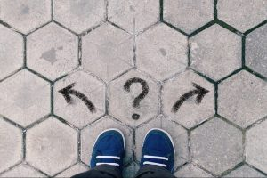 top view of blue shoes on tiled pavement with question mark and two arrows, concept of career crossroads