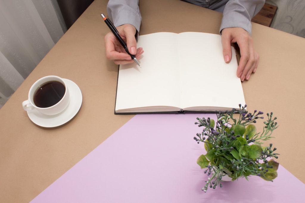woman writing her career development goals on a journal